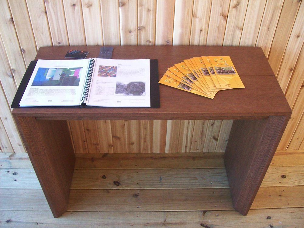 Display table with artwork descriptions binder and Alf House pamphlets.