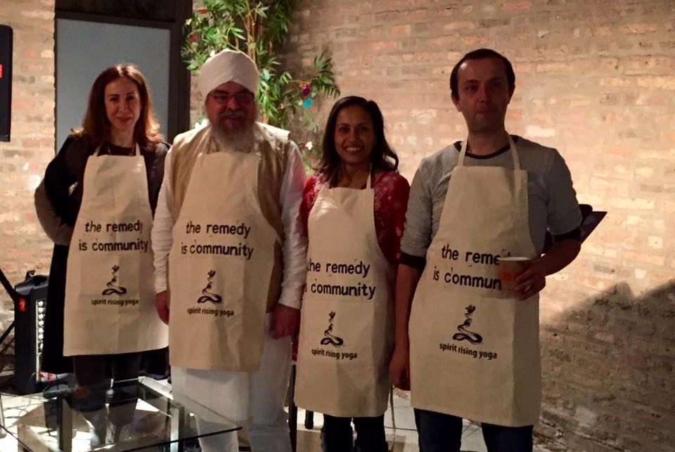 The winners of the Veggie MasterChef Challenge and their aprons featuring 'the remedy is community.'