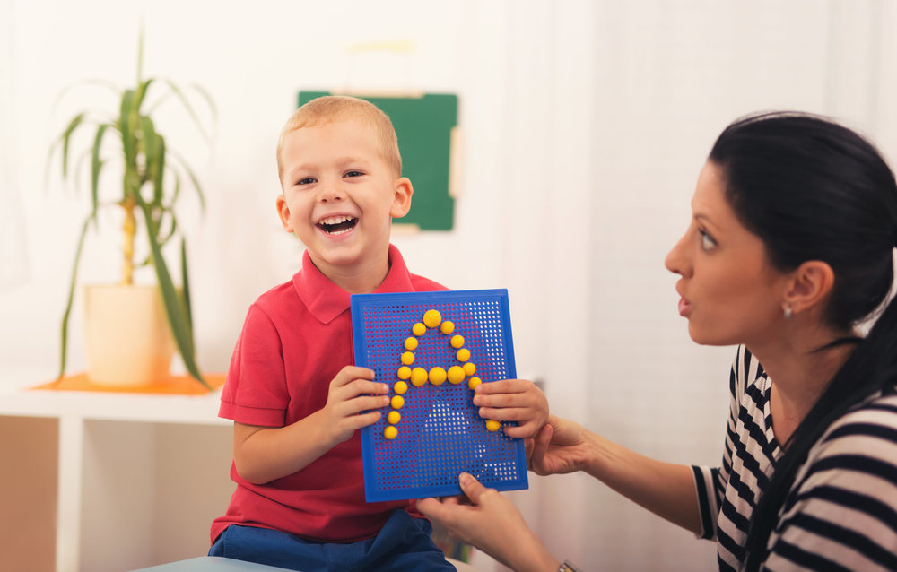 Little boy during lesson with his speech therapist.jpg