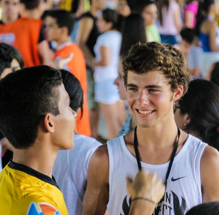 A team-member talks about sports with a Brazilian.