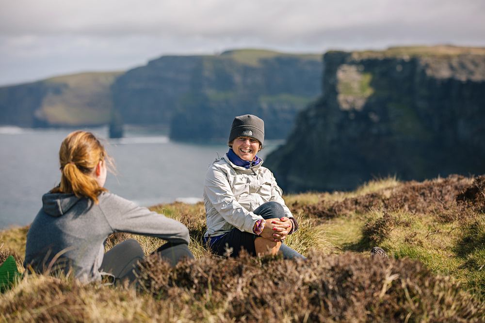 Leslie and Lucy soaking up some post-run sun by the Cliffs of Moher