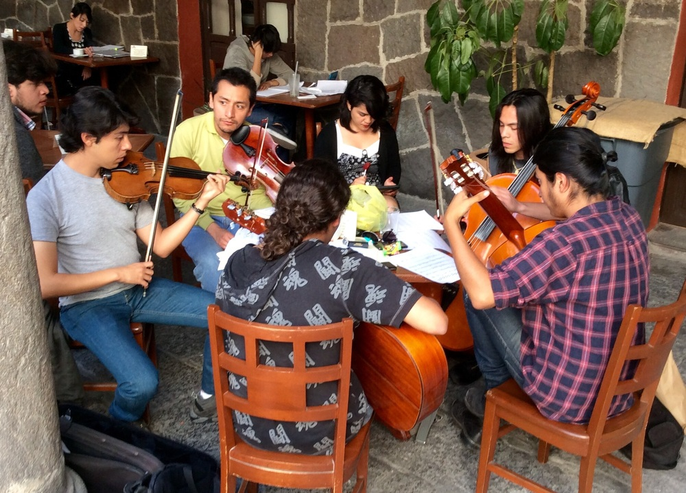Classical music students practicing in the courtyard of a cafe.