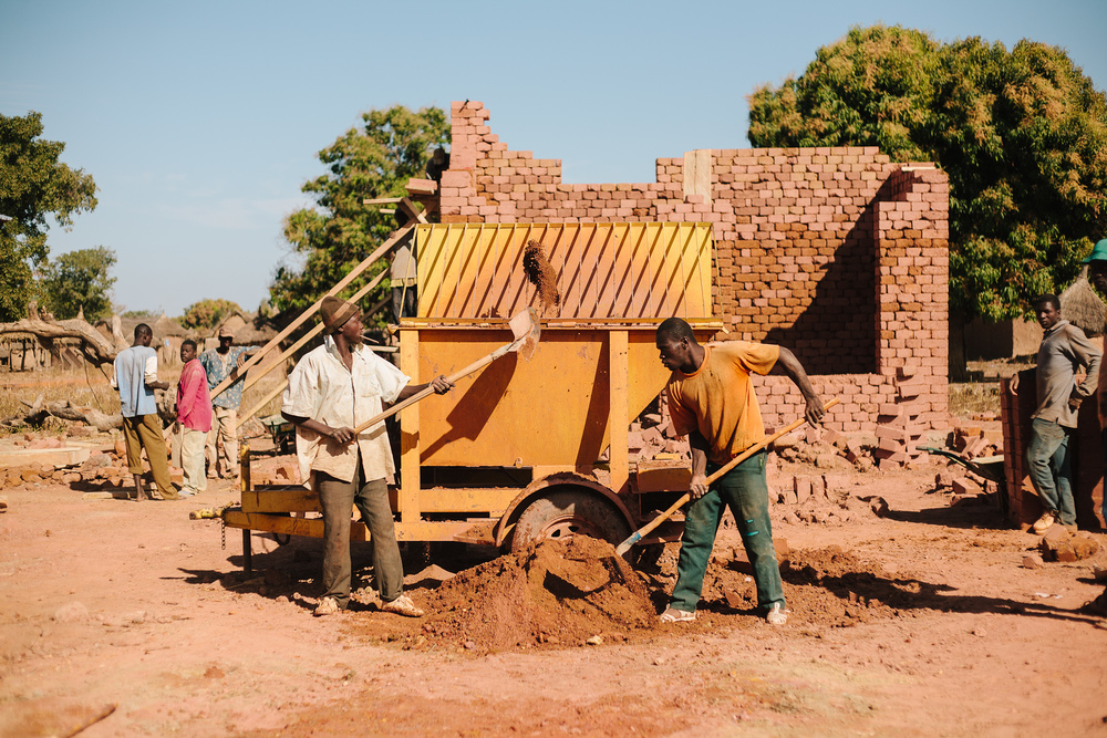 As the school's dedication day approaches, construction crews work to finish Beneko's middle school. Mali Rising schools are constructed with compressed brick technology, using on-site raw material to make adobe bricks that have the added benefit of regulating classroom temperatures.