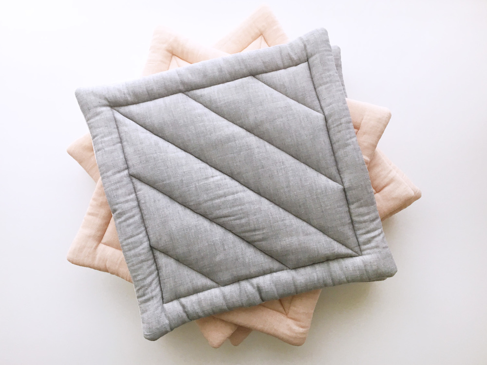 quilted cat mats in pebble grey and cherry blossom