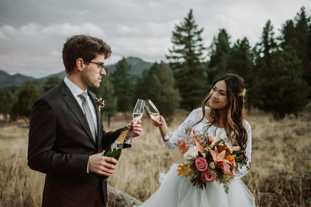 A couple cheers with champagne in their romantic boho mountain wedding elopement.