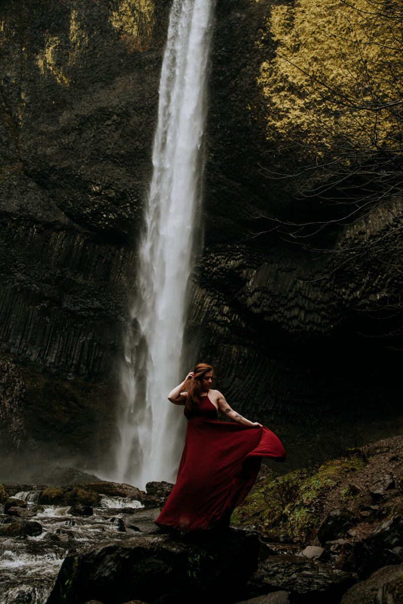 This red dress and fall colors perfectly illustrate our moody waterfall photoshoot in the pacific northwest.
