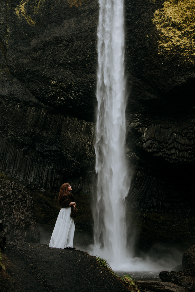 A bride stands in front of an epic waterfall in Portland.