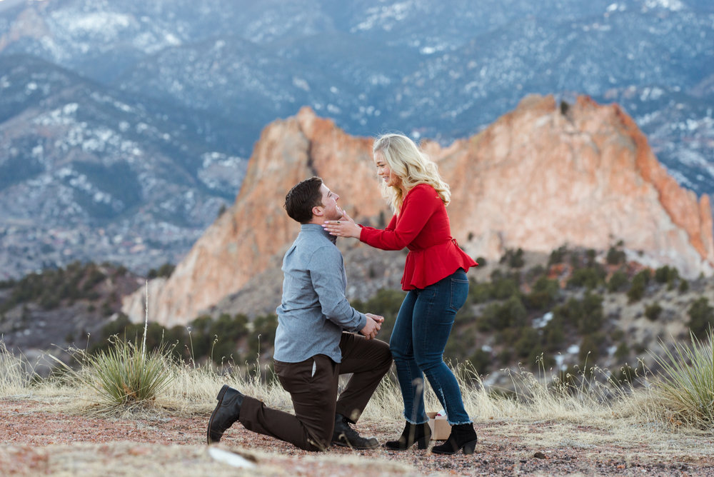 Christine embraces Blaine after he proposes with the Colorado mountains in the background.