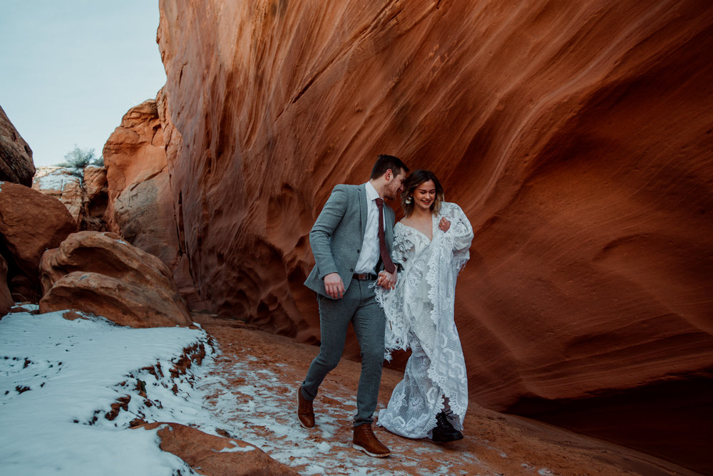 A newlywed bride and groom running through Arizona slot canyons on their wedding day.