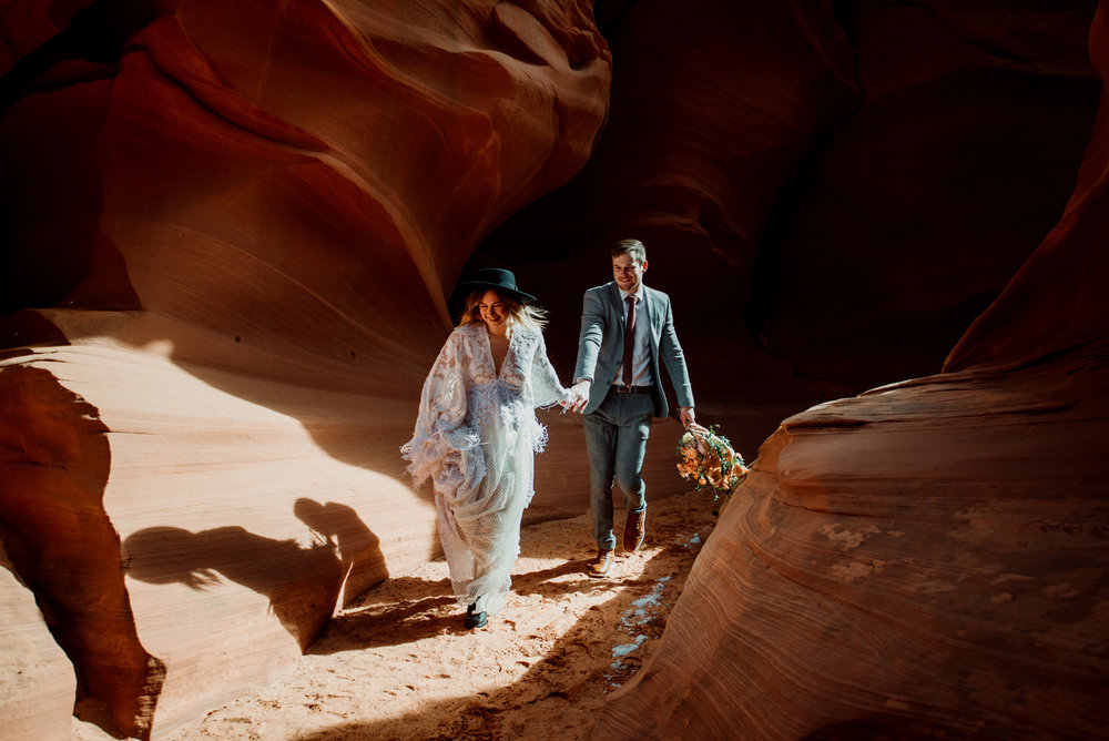 This photo shows a bride and groom running through Arizona red slot canyons.