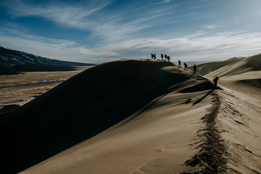 Photographers scale the tall sand dunes at Great Sand Dunes National Park.