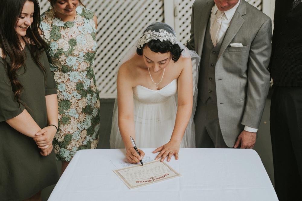 bride signing marraige certificate