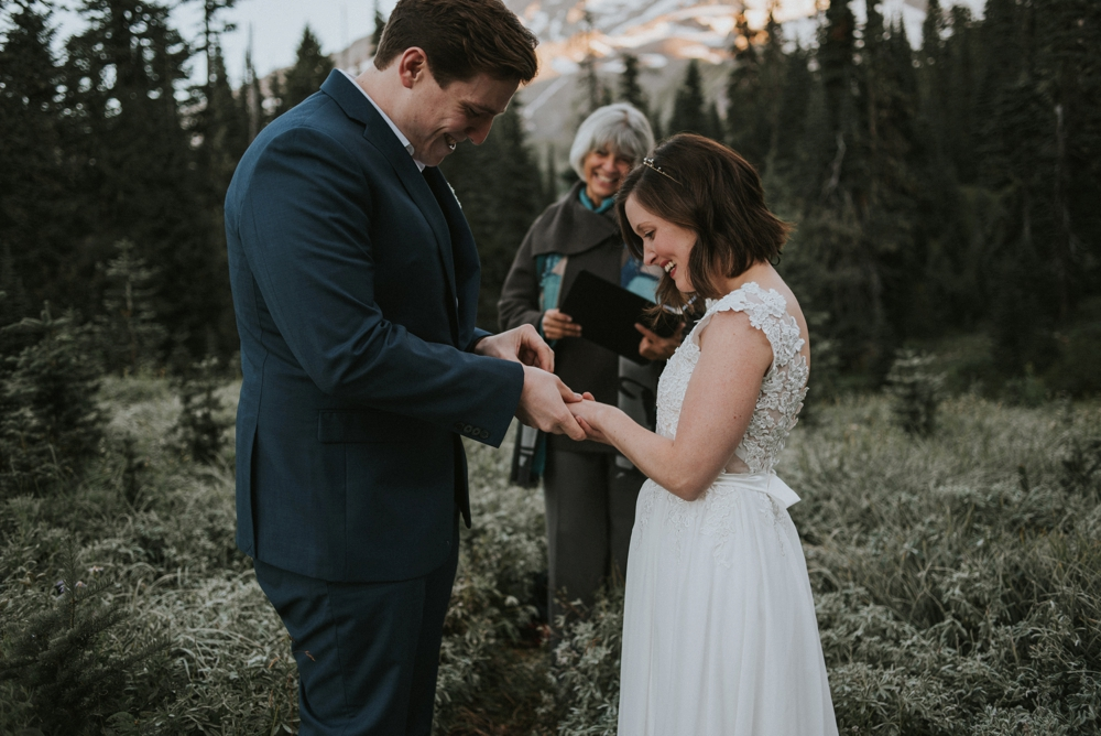 groom putting ring on bride