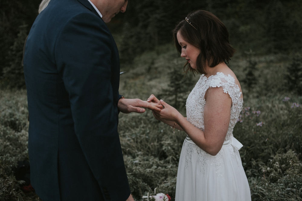 bride puts on grooms ring