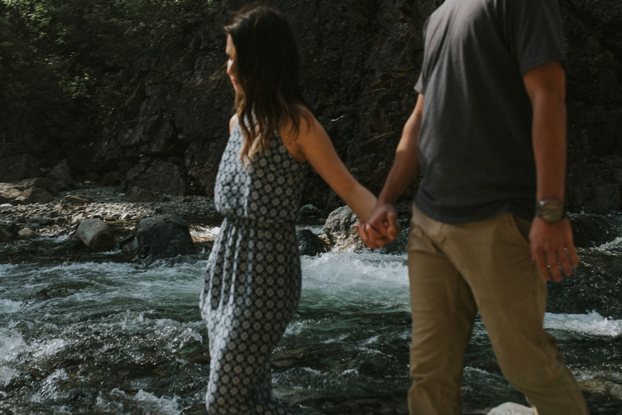 couple holding hands at river