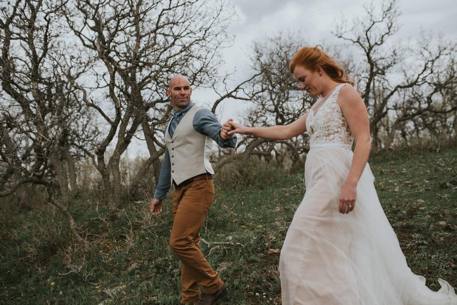 groom leading bride through woods