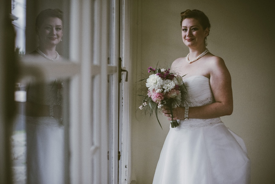 bride holding bouquet in window light seattle wedding photographer