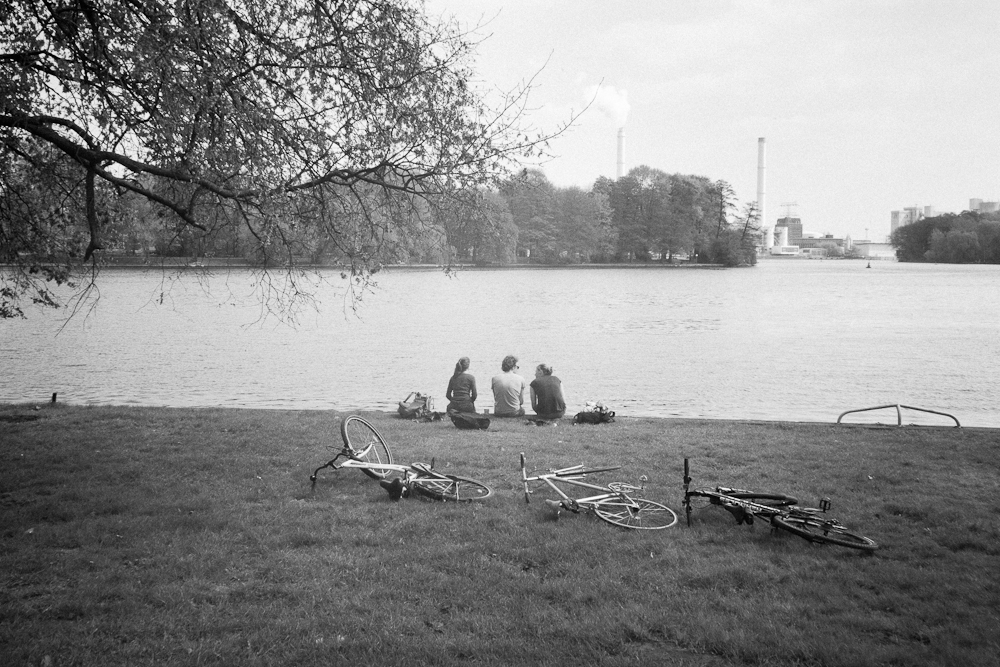 I am quite happy with my new  Loreo lens in a cap Perspective Control lens . No focus, ƒ11 or f22 and crappy glass.   And i quite like this shot of three people with their bikes sitting by the river under a tree with some factories in the background.