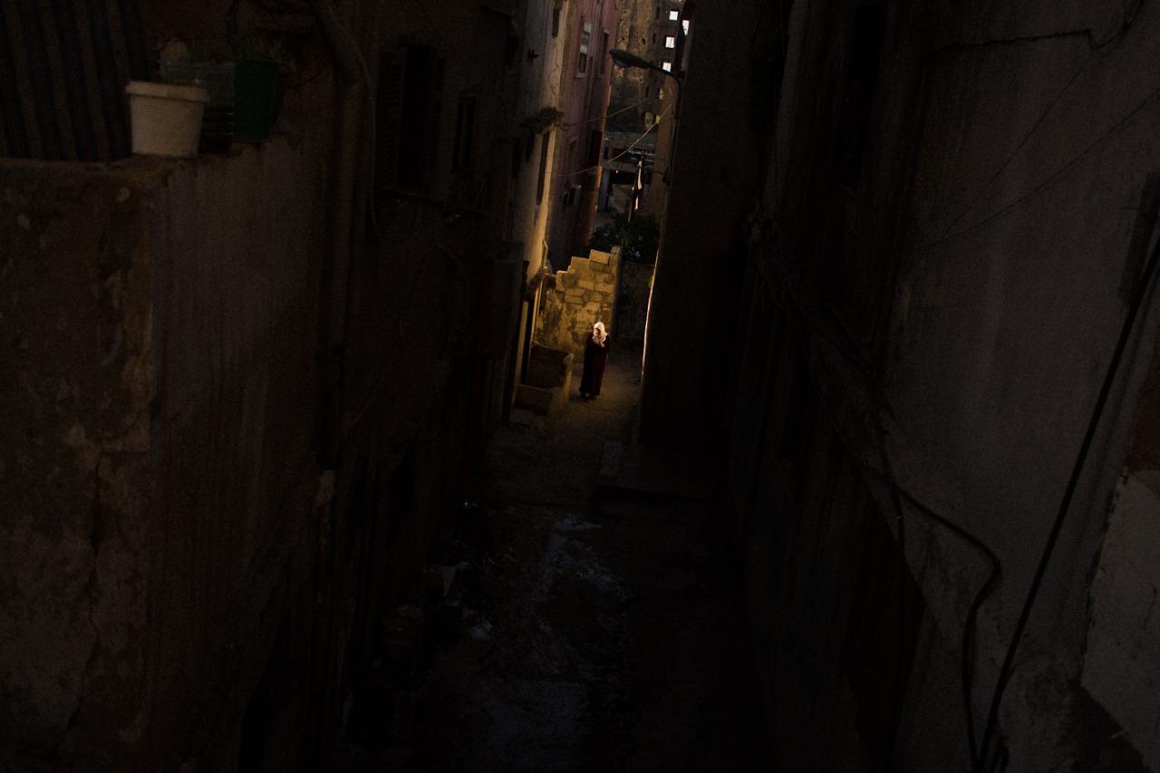 Tripoli (Lebanon) January 14th 2013. An old woman walking in a side street between an Alawi and a Sunni neighborhood.