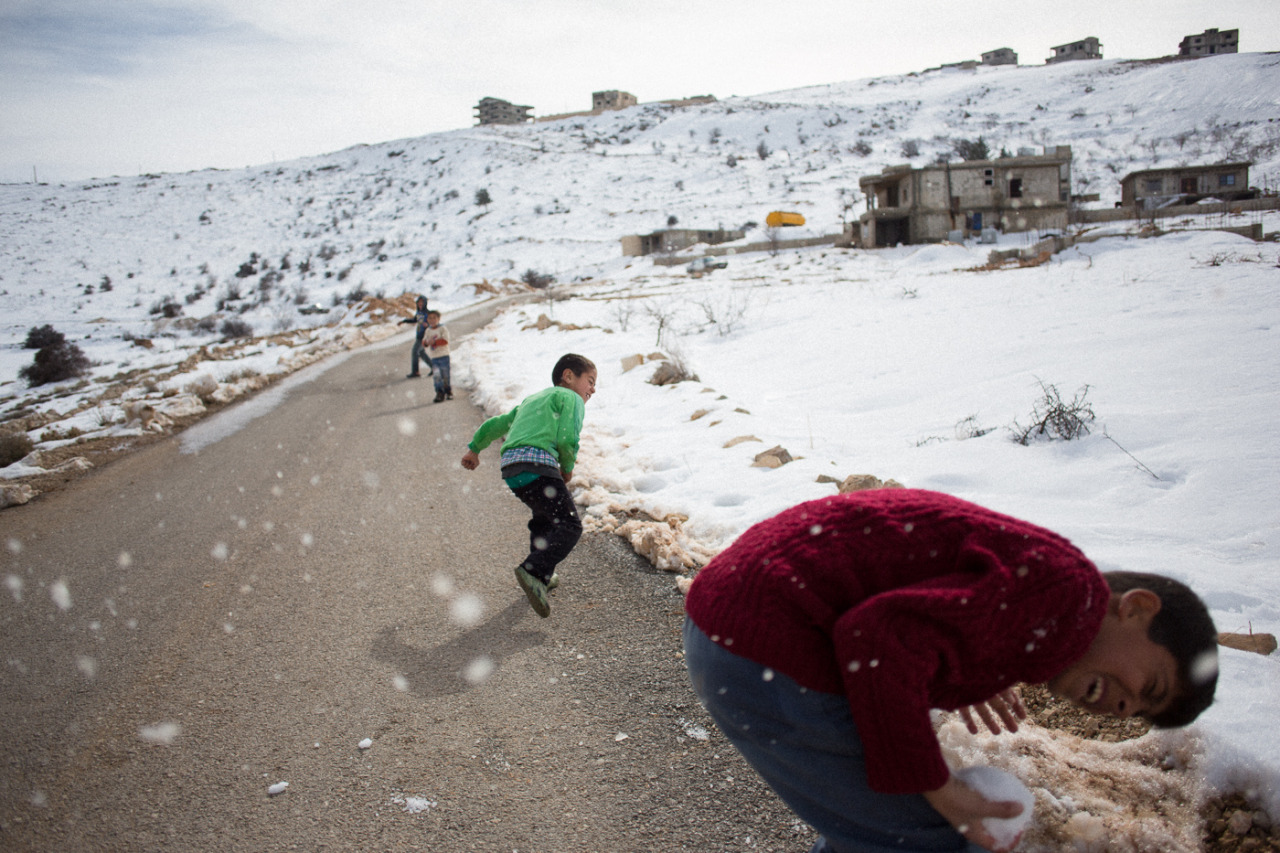 Syrian kids throwing snow balls at each other. Abou Ismail refugee camp in Arsal, Lebanon (near the Syrian border). January 2013 more pictures from the camp in next blogpost