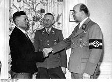 Heinz Reinefarth (w środku) wraz z Arthurem Greiserem  wita milionowego Niemcaprzesiedlonego doKraju Warty  w ramach niemieckiej akcji przesiedleńczej Heim ins Reich   – marzec 1944 (źródło: Bundesarchiv)