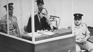 Adolf Eichmann robiący notatki podczas swojego procesu w Jerozolimie. Szyby z kuloodpornego szkła miały chronić go przed zabójstwem (źródło: wbur.org)