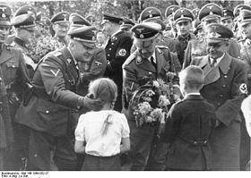 Przyjmowanie kwiatów od dzieci. Od lewej: SS-Gruppenf  ü  hrer   Wilhelm Koppe, Heinrich Himmler i Gauleiter Fritz Bracht (źródło: wikipedia.org)