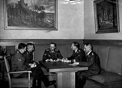 Heinrich Müller (pierwszy z prawej) podczas narady kierownictwa niemieckiej policji; obok niego siedzą od lewej: oficer SS Franz Josef Huber, szef Kripo Arthur Nebe, szef SS i policji Heinrich Himmler i szef RSHA Reinhard Heydrich, listopad 1939 (źródło:  Bundesarchiv Bild )