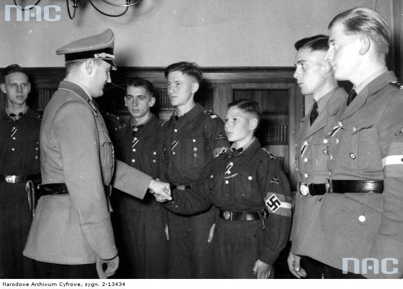 Artur Axmann wręcza członkom Hitlerjugend Wojenny Krzyż Zasługi z Mieczami, zaś szesnastoletniemu Nikolausowi Willms (trzeci z prawej) Krzyż Żelazny II klasy (źródło:  www.audiovis.nac.gov.pl )