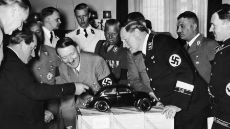 Ferdynard Porshe (left), Adolf Hitler and Volkswagen engineers while discussing the prototype of the car.
