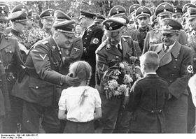 Receiving flowers from children, from the left: SS-Gruppenführer Wilhelm Koppe, Heinrich Himmler i Gauleiter Fritz Bracht (source:  wikipedia.org )