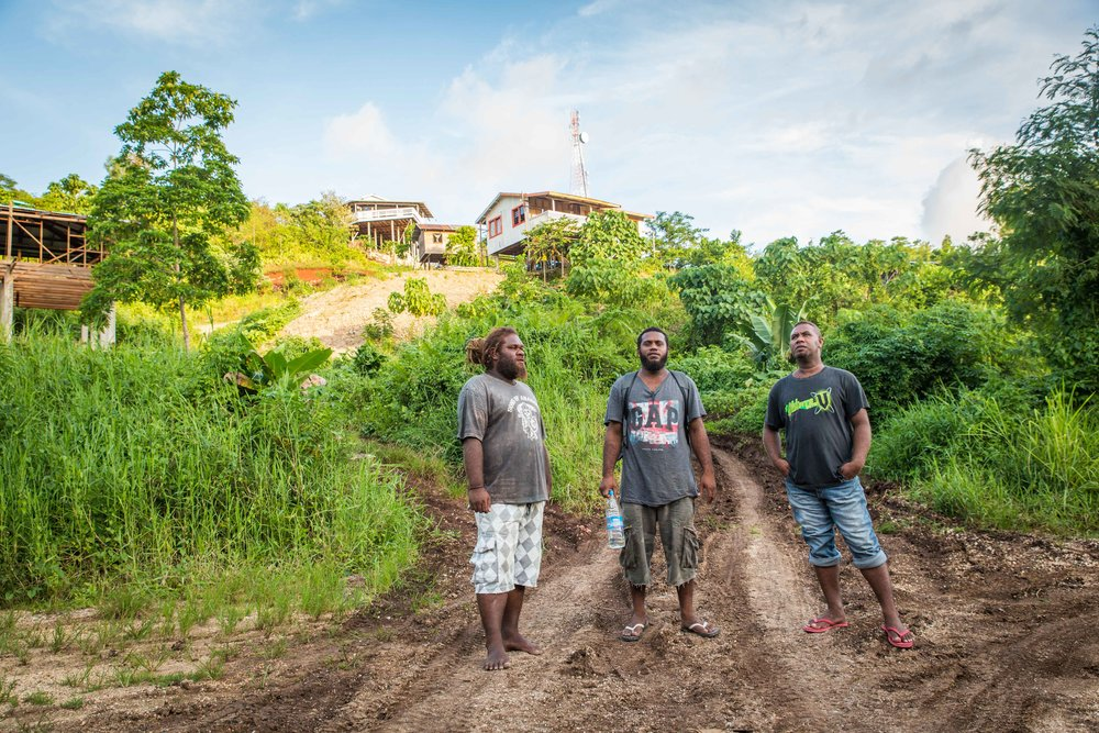 Ayexz (L), Richard (C) and David (R) pause on the way to down to the bore hole. They say waste from the houses on the hill in the background is going into the water source.