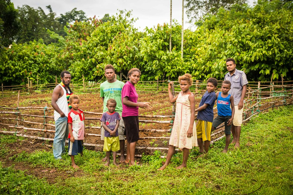 Derick and other young people in the village in front of their peanut farm