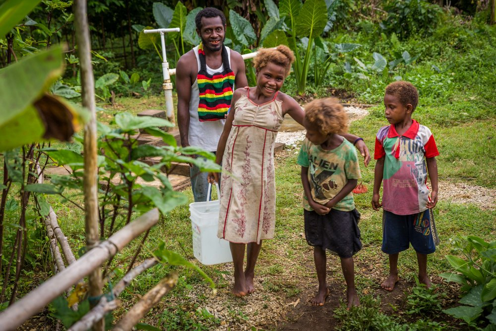 Derick and his children carry water back from the new pump. Namoabu village no longer has water shortages in dry season.