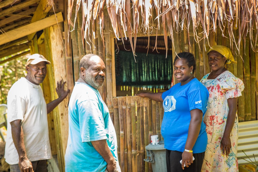 Anicka with the village chief (left), her dad and mum in front of the new house.