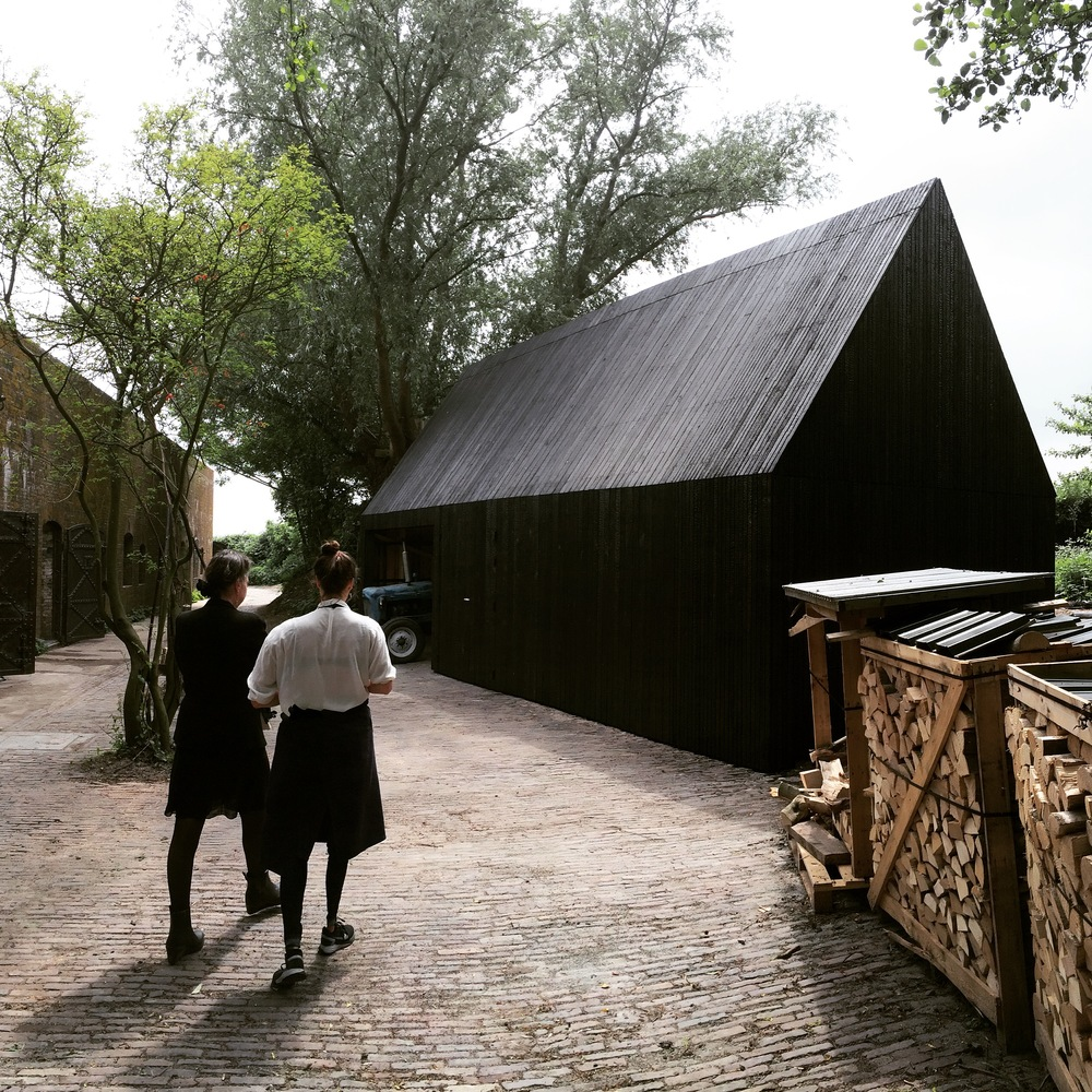 The shed with the island's sustainable installations, clad in burnt wood, a Japanese preservation technique called Shou Sugi Ban.