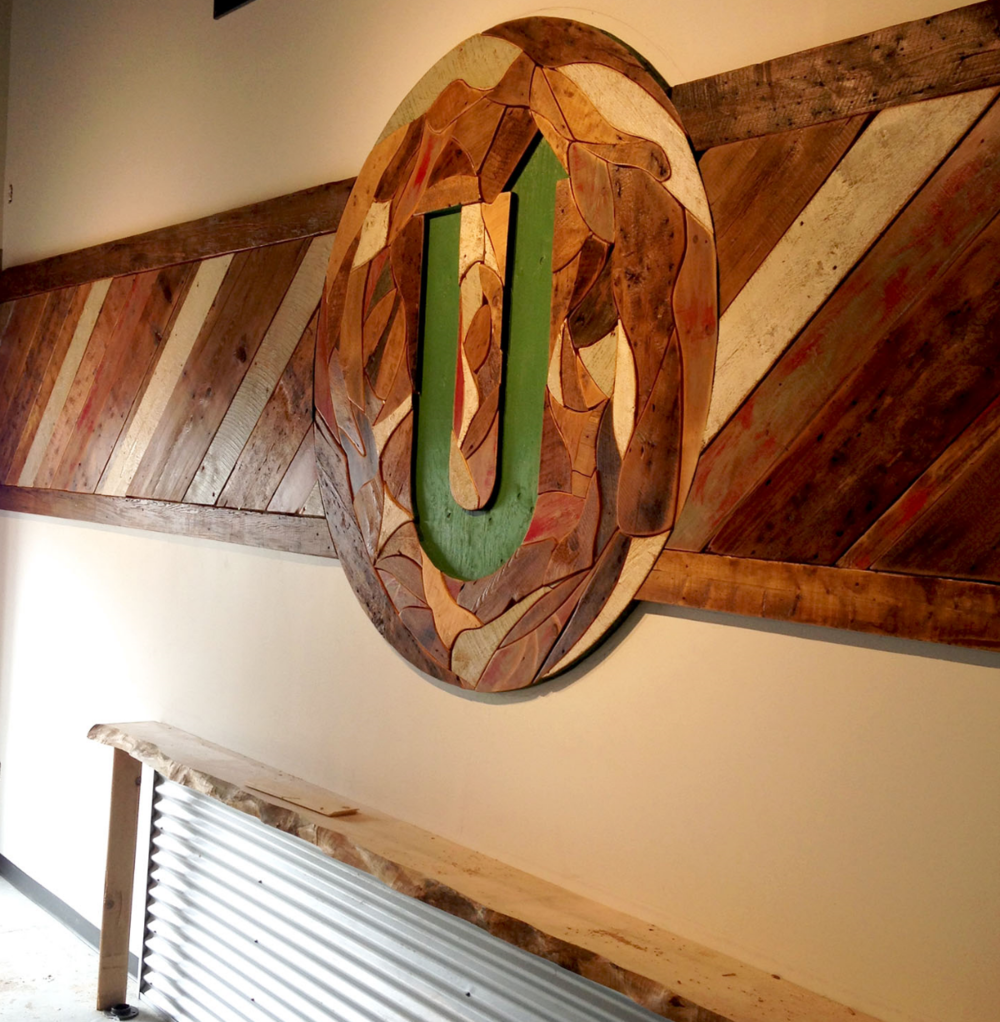Upstreet logo embedded into reclaimed wood feature wall.