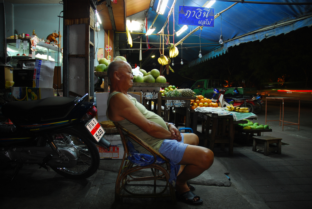A plump fruit seller patiently waiting for an unsuspecting hippie to fall into his health food trap!  Chang Mai