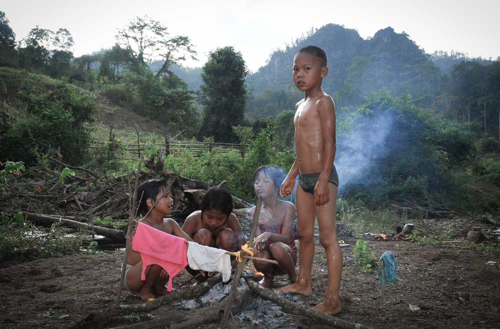 "Children drying their clothes, by a little fire they built on the bank of a stream, after a swim. Not many of us in the ""West"" would allow such a thing to happen anymore sadly.  Jungle trek -northern Thailand"