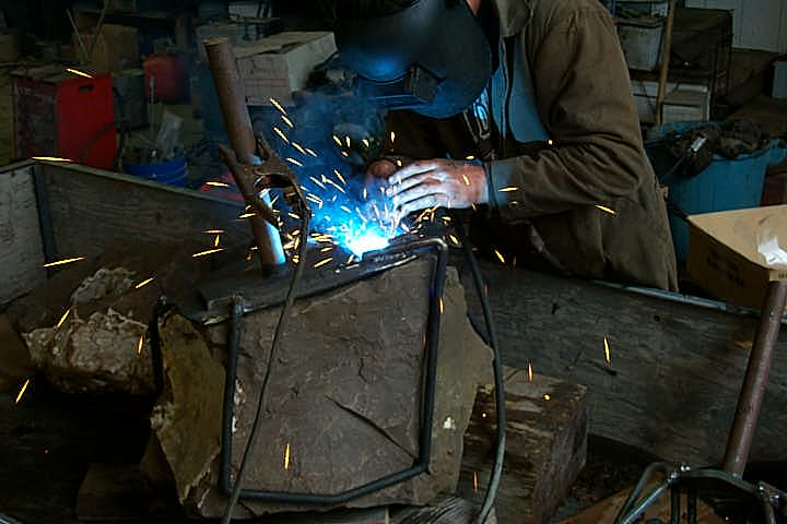 Tellel Waldhaus welding a steel encasing onto one of three Drusy Quartz specimens.