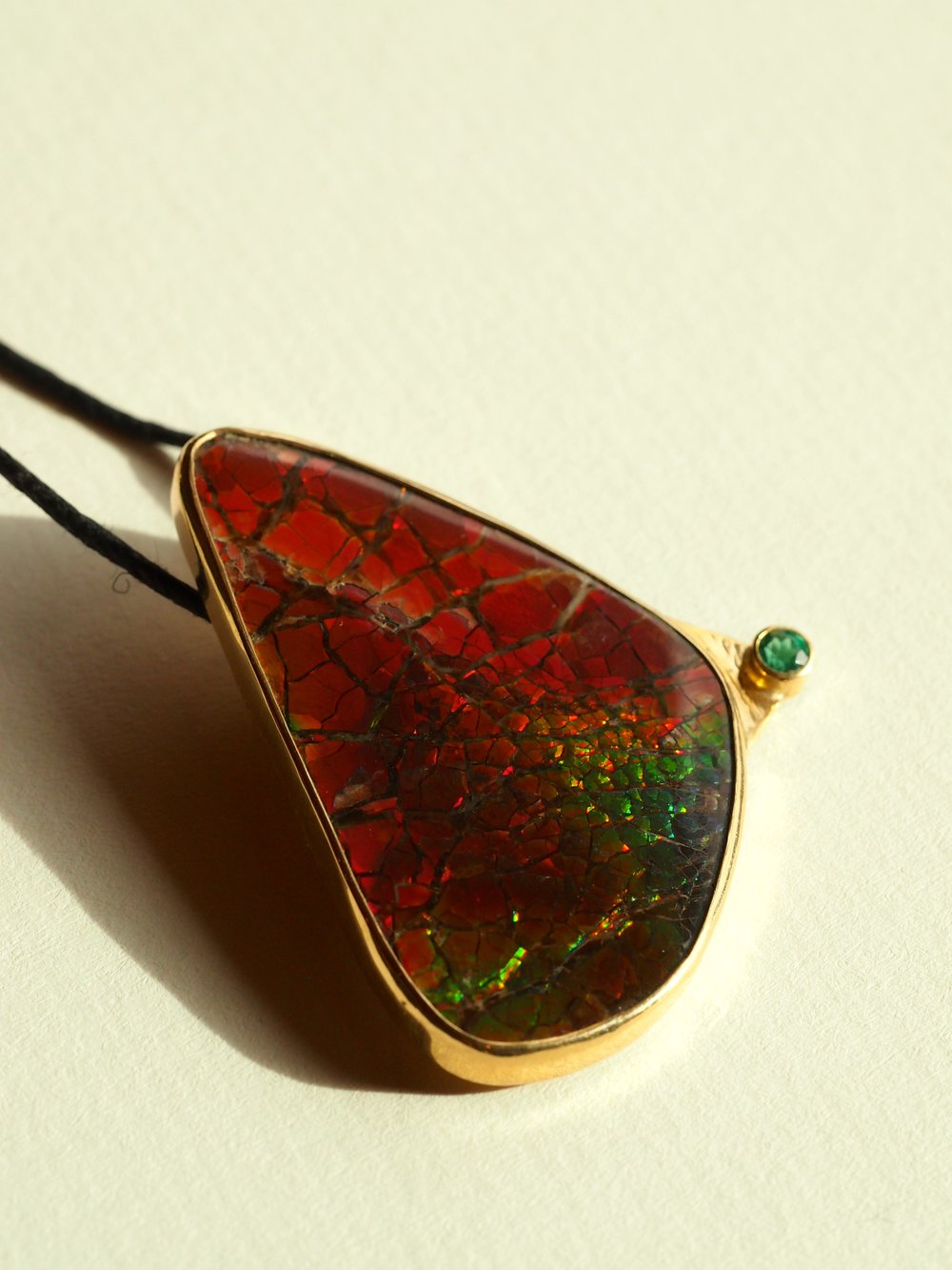 Canadian Ammolite Pendant with Emerald, set in 14k Gold. Available for purchase.