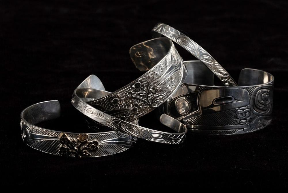 A variety of sterling silver and 14K gold bracelets in widths ¼ inch, ½ inch. ¾ inch, 1 inch, by Haida artists, Carmen Goertzen and son Neil Goertzen.
