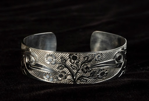 This 3/4 inch wide by 6 1/2 inches long bracelet was created by Haida artist Carmen Goertzen. The design is two hummingbirds feasting on local salmonberry flowers.