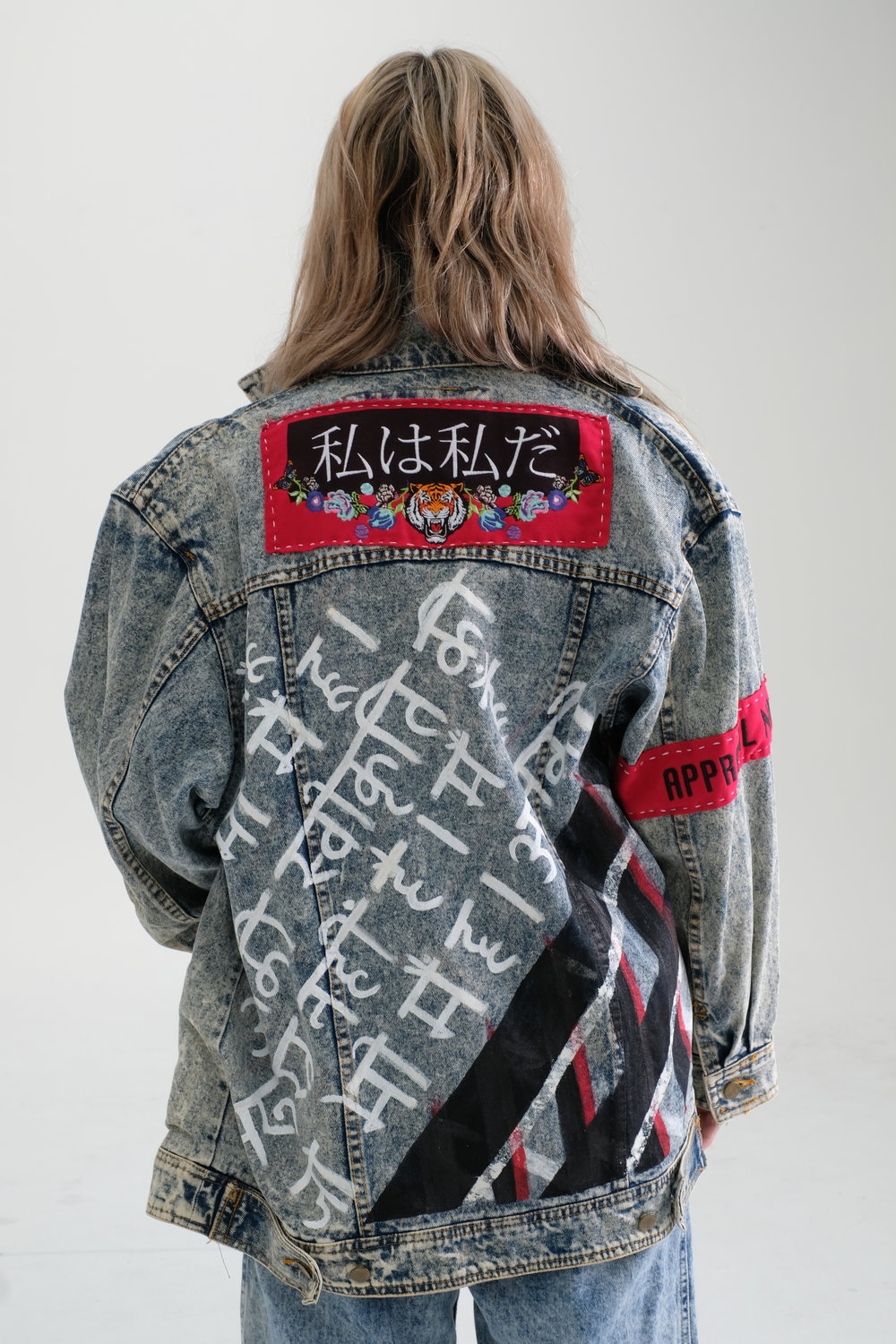 The back of our vintage recycled jacket, we have really gone to town with this one! Hindi transcript translated in to english reads 'I am who i am. Your approval is not needed; with a modern striped painted pattern underneath to add a modern twist. The back top has Japanese text embroidery which translate to read 'I am who i am.' with our bespoke floral and tiger artwork that has loads of colours involved.