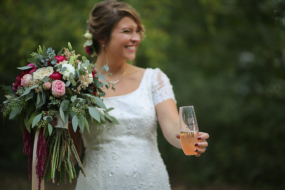 Bride Holding her Bouquet and Champagne Brittany + Michael's Camp Themed Wedding | Virginia Wedding Photographers