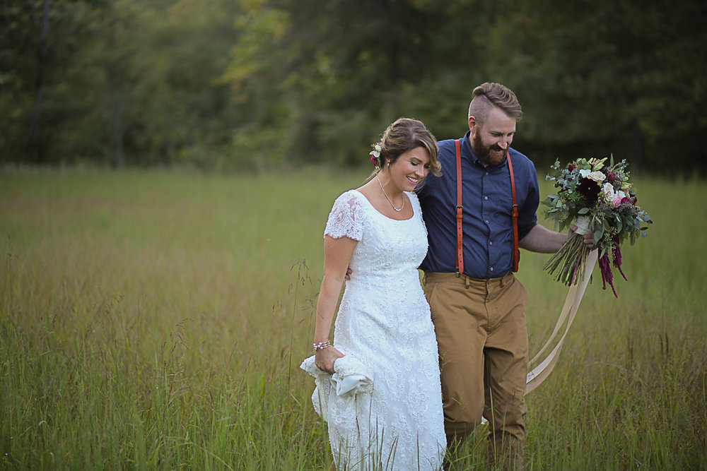 Bride and Groom Walking Through a Field of High Grass Brittany + Michael's Camp Themed Wedding | Virginia Wedding Photographers