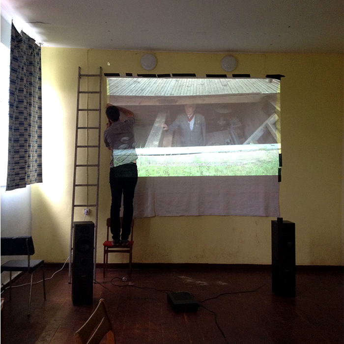Nick hangs a bed sheet on the walls of an abandoned Soviet schoolhouse for our village screening.