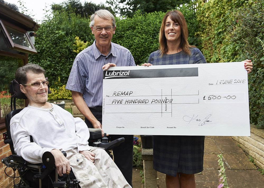 From left, Richard Shaw, who has a muscle-wasting disease and has benefitted from the work of Remap, and Remap volunteer Mike Banks receive a donation for the charity for £500 from and Jane Spencer, secretary of Hazelwood chemical company Lubrizol's Charities and Community Committee.