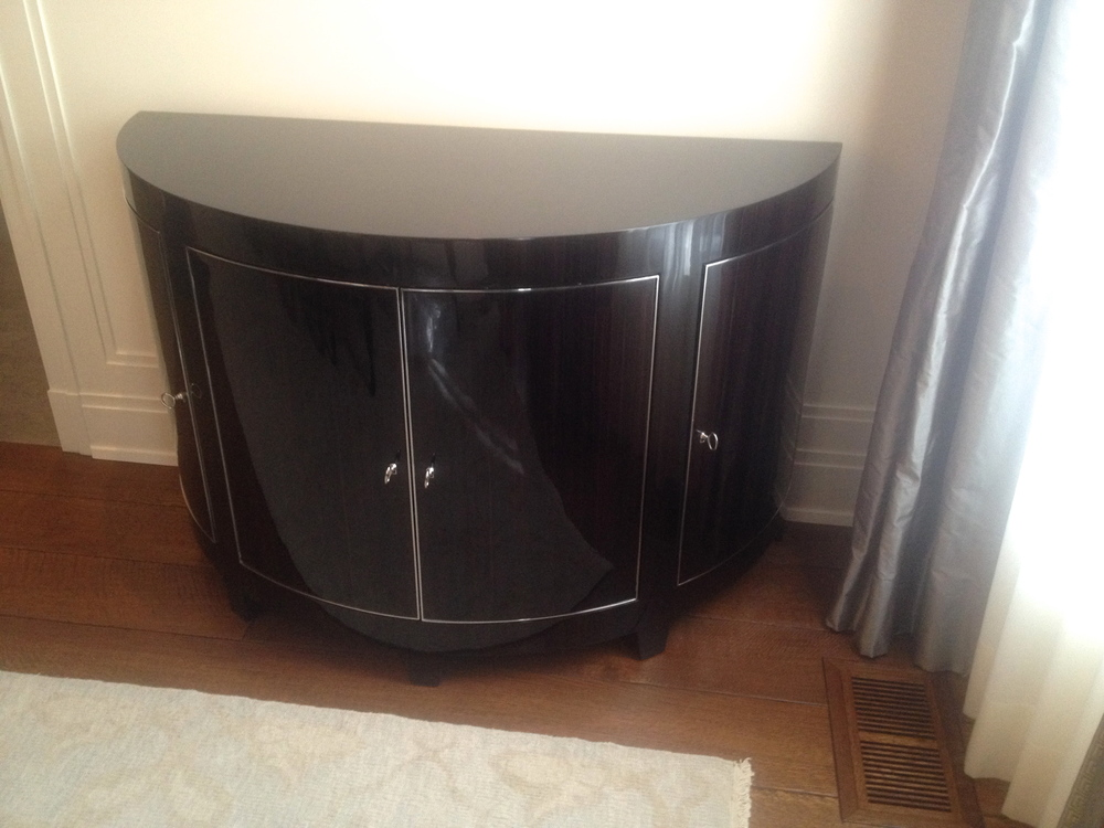 TRU custom design and fabrication of curved console. Macassar ebony high gloss polyester resin full filled polished finish with polished nickel door trim inlay.