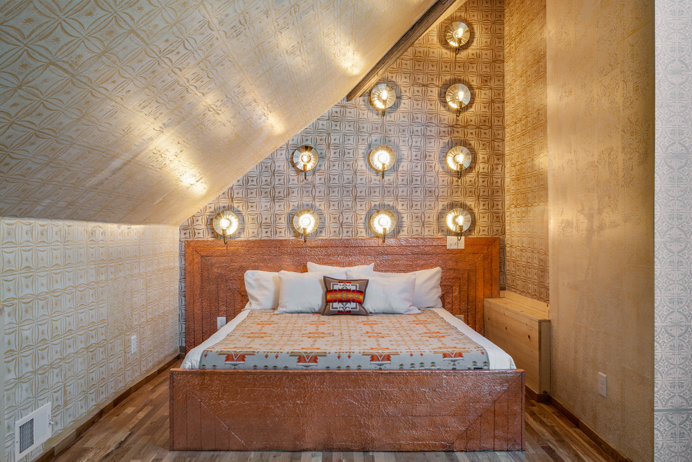 Reclaimed wood bed with patterned copper head and footboards in 'The Muse' Bedroom.